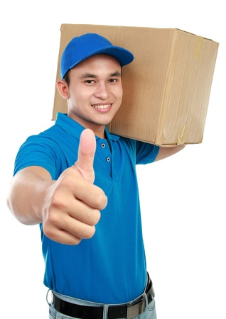 delivery man: smiling delivery man in blue uniform carrying packages while gesturing thumb up sign isolated on white background