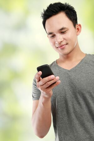 man phone: close up portrait of happy young man reading a message Stock Photo
