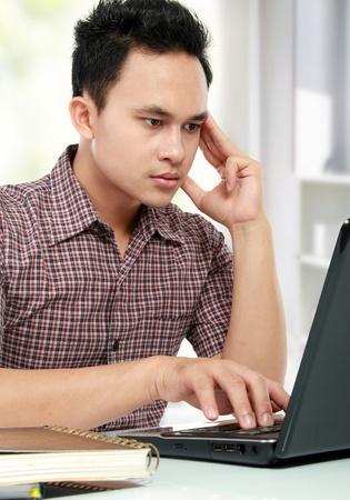 retrato de concentrar hombre joven que trabaja con la computadora portátil en su escritorio