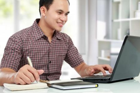 usando computadora: Retrato de hombre joven que trabaja con la computadora port�til en su escritorio Foto de archivo
