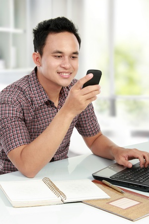 young man using a laptop and texting on mobile phone in his house photo