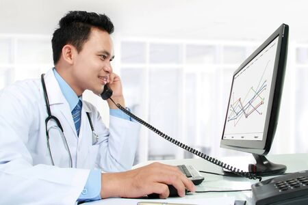 portrait of medical doctor working with his computer photo