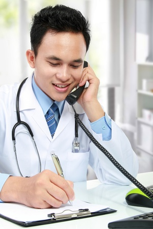 phone professional: young asian medical doctor writing a note while calling on the phone