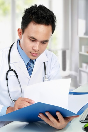 portrait of medical doctor reading a report document at his office photo