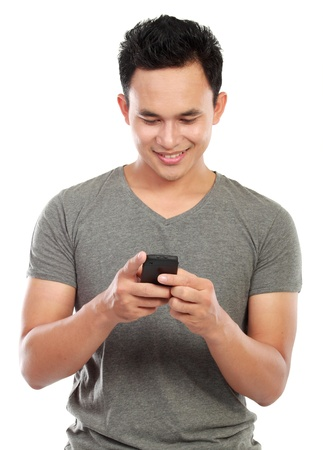 texting: young asian man texting message at his mobile phone isolated over white background