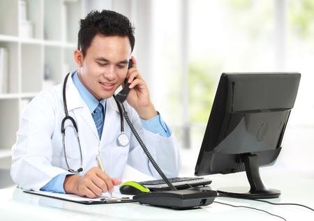 彼の机で男性医師多忙な仕事の笑みを浮かべてください。