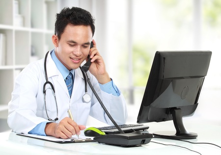 llamando: de trabajo sonriendo médico masculina ocupada en su escritorio