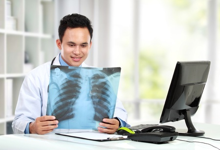potrait of doctor looking at chest x ray photo