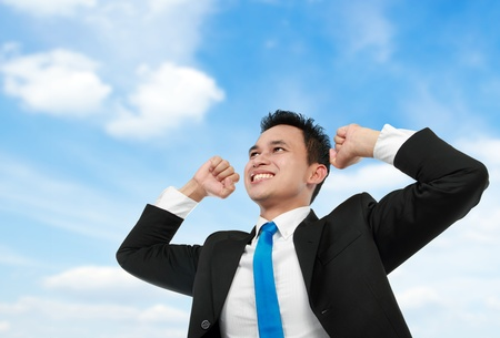 Cheerful asian business man with arms raised under the blue sky photo