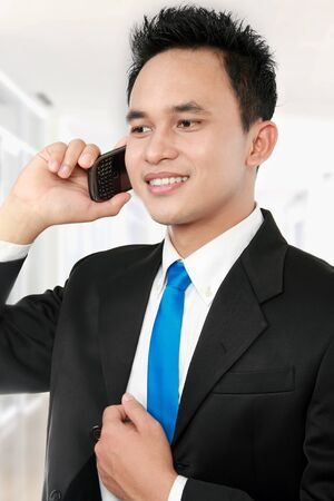 close up portrait of Handsome business man calling by phone at the office photo