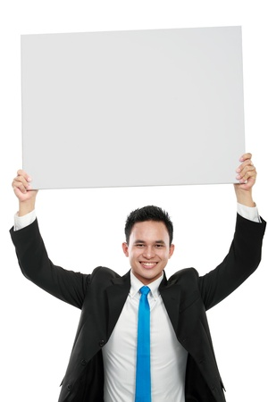 Portrait of a smiling young business man holding a blank billboard on top of his head photo
