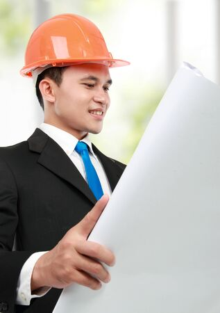 confident Handsome young asian man architect looking at paper print in the office photo