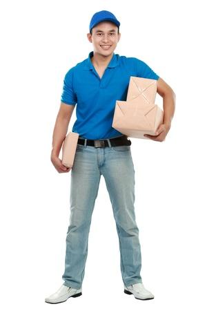 cartero: retrato de cuerpo entero de mensajer�a hombre de uniforme azul con un mont�n de paquetes aislados en blanco Foto de archivo