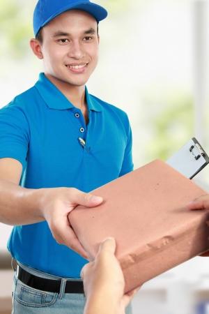 cartero: Mensajer�a hombre joven en uniforme azul dando a los paquetes Foto de archivo
