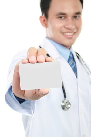 Young doctor holding business blank card. Isolated on white background photo