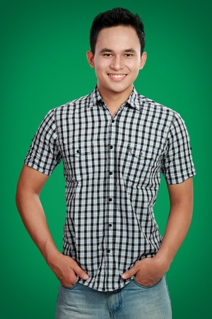 hand in pocket: portrait of happy asian male smiling against green backgrounds
