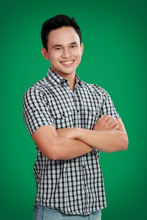 portrait of happy asian male smiling against green backgrounds photo