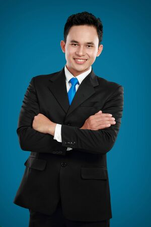 Portrait of a confident asian business man smiling against blue background Stock Photo - 12809614