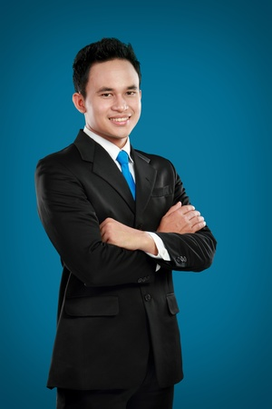 Portrait of a successful asian businessman smiling against blue background Stock Photo - 12809615