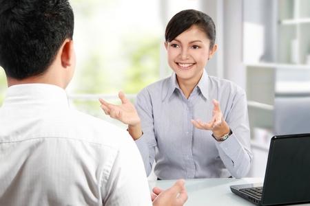 Lachende mensen praten over zakelijke bijeenkomst op het kantoor