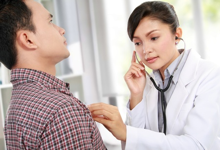 female doctor taking the heartbeat of her patient Stock Photo - 12809749