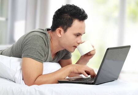 A young man lying on a bed and using a laptop computer while drinking coffee photo