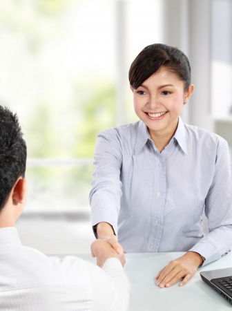 Pretty asian business woman shaking hands with a man in her office photo