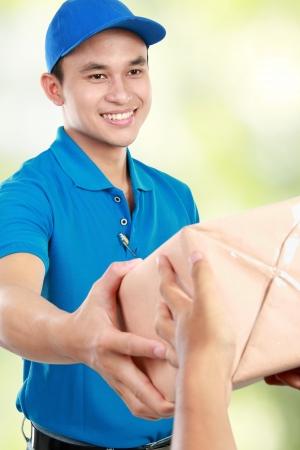 corriere: Corriere Giovane uomo in uniforme blu dando un pacchetto