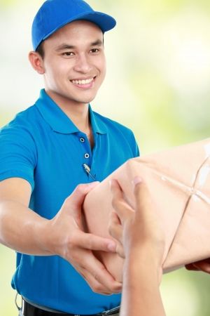 delivery man: Young man courier in blue uniform giving a package