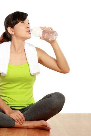 Portrait of healthy fitness woman holding a bottle of water in the gym photo
