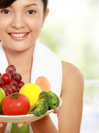 close up portrait of healthy fitness woman carrying a group of healthy food photo