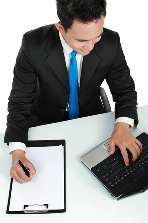 Portrait of a handsome young business man with laptop and pen working photo