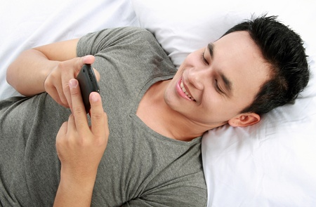 young asian man texting a message with his cell phone while laying on bed photo