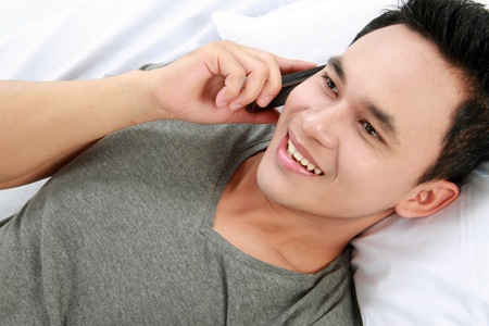 personas comunicandose: hombre joven asiático que habla en su teléfono mientras estábamos tumbados en la cama