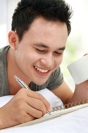Asian male writing on his diary while lying on the bed photo