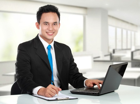 asian on laptop: Portrait of a handsome young business man working in the office