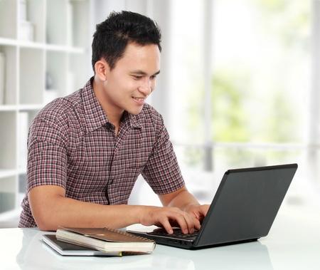 laptop asian: Retrato de hombre joven que trabaja con la computadora port�til en su escritorio Foto de archivo