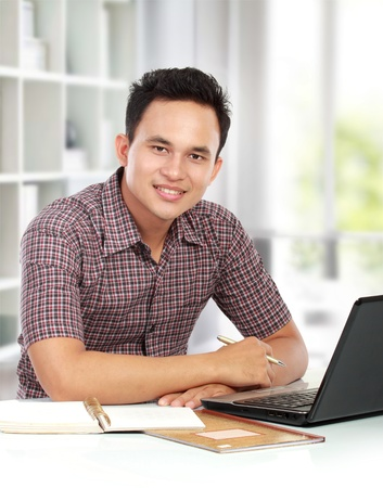 portrait of young man working with laptop at his desk photo