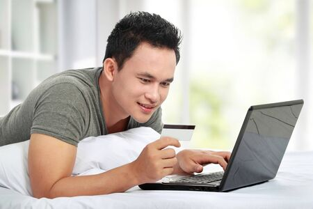 bank rate: man purchasing product online, using credit card to pay Stock Photo