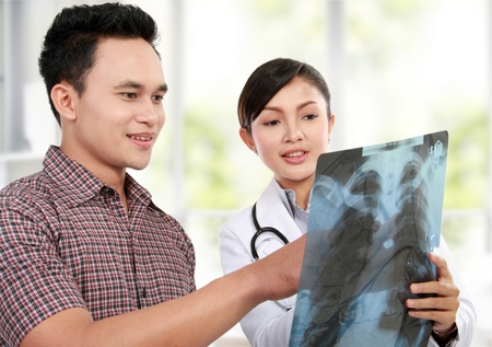 Asian female doctor explaining lung xray to patient photo