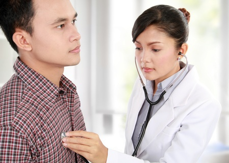 check up: female doctor checking patient heartbeat using stethoscope Stock Photo