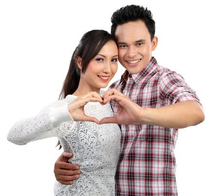 Happy young couple in love showing heart with fingers isolated over white background Stock Photo - 12991745