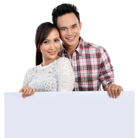 holding blank sign: Young couple holding blank banner isolated over white background