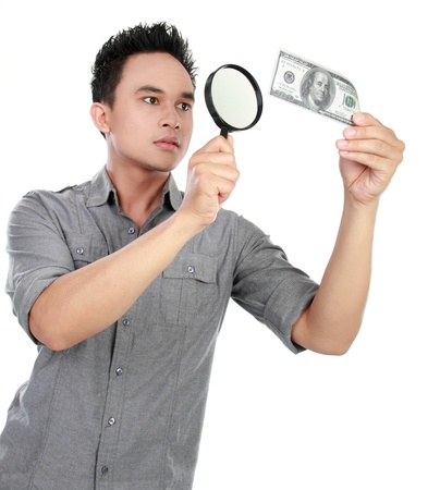 portrait of young man looking dollar bill through a magnifying glass over white background photo