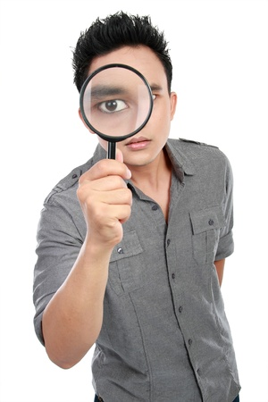 portrait of young man looking through a magnifying glass isolated over white background photo