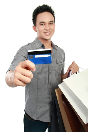 young man with shopping bags and credit card isolated on white background photo