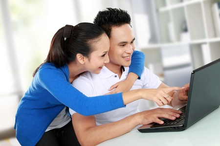 Portrait of smiling young couple using a laptop photo