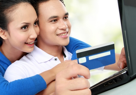 portrait of happy couple shopping online at house photo