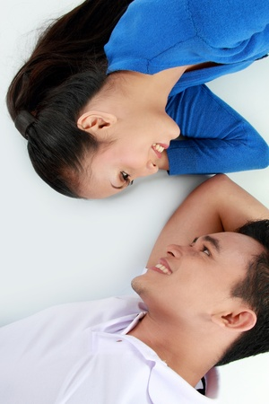 young lovely couple lying on the floor, happy smile looking to each other, top view photo