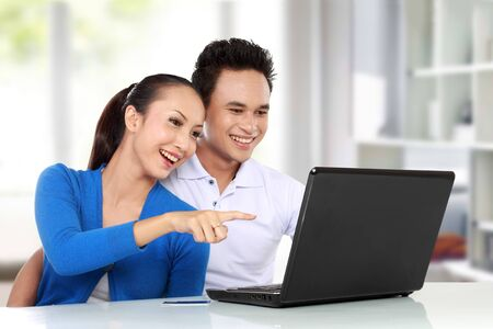 Portrait of happy young asian couple using a laptop photo